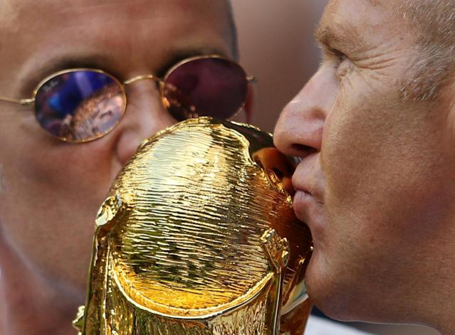 <p>Fans kiss a World Cup replica inside the stadium before the match </p>