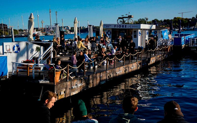 People enjoy the weather on a floating bar at Stranvagen in Stockholm on September 19, 2020, during the novel coronavirus COVID-19 pandemic - Jonathan Nackstrand/AFP