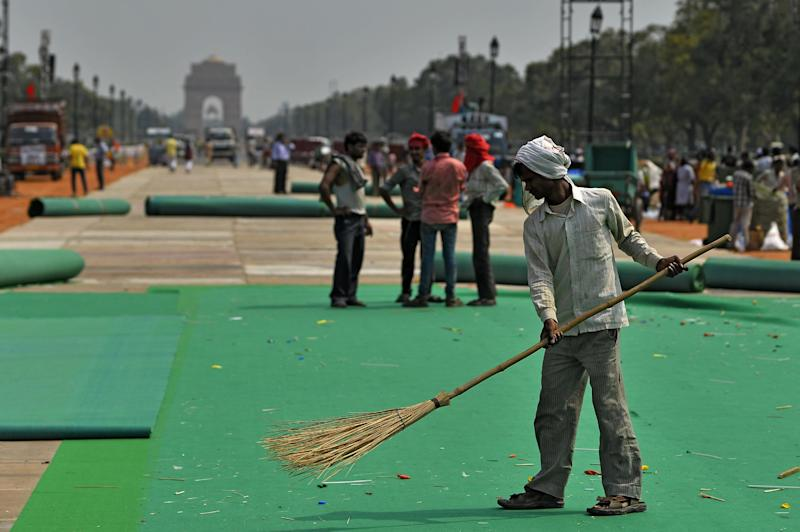 A resident sweeps a carpet at the launch of a Clean India Campaign by Prime Minister Narendra Modi in New Delhi, October 2014. A politician faces flak over a staged cleaning photo
