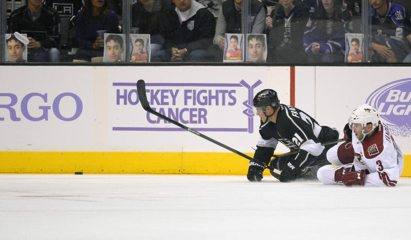 Los Angeles Kings right wing Matt Frattin, left, and Phoenix Coyotes defenseman Keith Yandle, right, battle for the puck during the first period of their NHL hockey game on Thursday, Oct. 24, 2013, in Los Angeles. (AP Photo/Mark J. Terrill)
