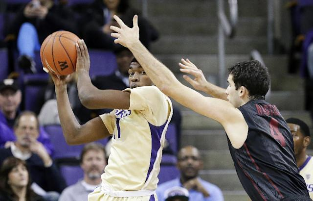 Washington's Mike Anderson, left, grabs a rebound in front of Stanford's Stefan Nastic in the first half of an NCAA college basketball game Wednesday, Feb. 12, 2014, in Seattle. (AP Photo/Elaine Thompson)