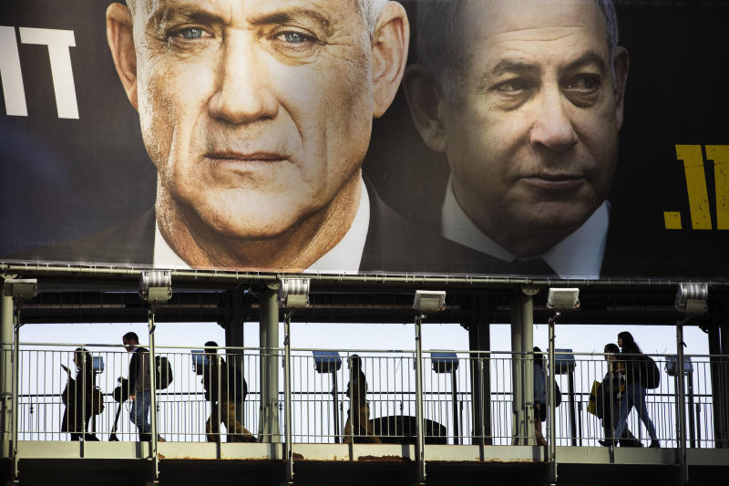People walk on a bridge under an election campaign billboard for the Blue and White party, the opposition party led by Benny Gantz, left, in Ramat Gan, Israel, Tuesday, Feb. 18, 2020. Prime Minister Benjamin Netanyahu of the Likud party is pictured at right. (AP Photo/Oded Balilty)