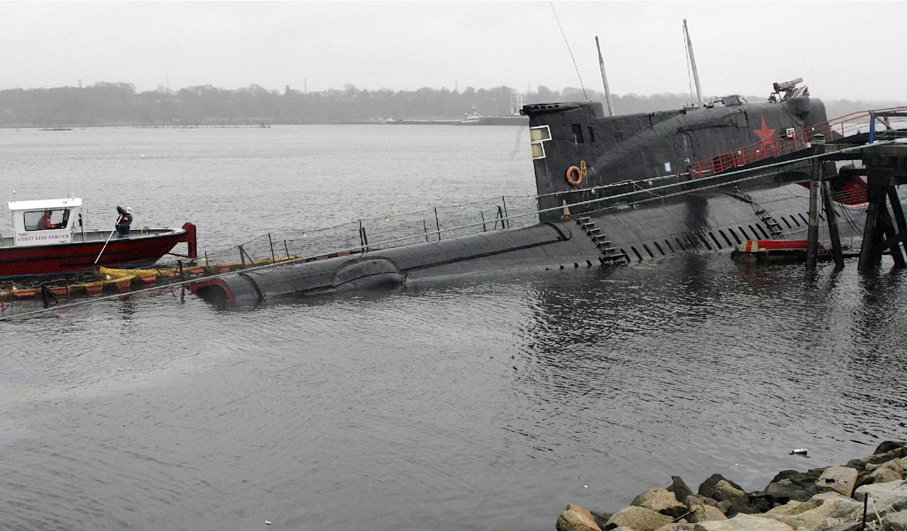 FILE - In this Tuesday, April 17, 2007 file photo, crews work to contain an oil spill from a Soviet submarine used as a floating museum at Collier Point Park in the Providence River in Providence, R.I. The submarine's bow was grounded and its stern was sinking after a nor'easter hit the east coast the preceding weekend. In 2009 the sub was moved to a nearby scrap metal facility, but the company stopped working on it in 2014. Rusted remnants remain in the river in August 2016, and the state wants them gone. (AP Photo/Stew Milne, File)