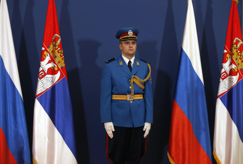 In this photo taken Thursday, Jan. 17, 2019, a member of the Serbian honour guard stands between Serbian and Russian flags during visit of Russian President Vladimir Putin in Belgrade, Serbia. Officials say on Monday, Aug. 26 Serbia will sign a free trade agreement with a Russian-led economic group, the move which could further hamper the Balkan country's proclaimed efforts to joining the European Union. (AP Photo/Darko Vojinovic)