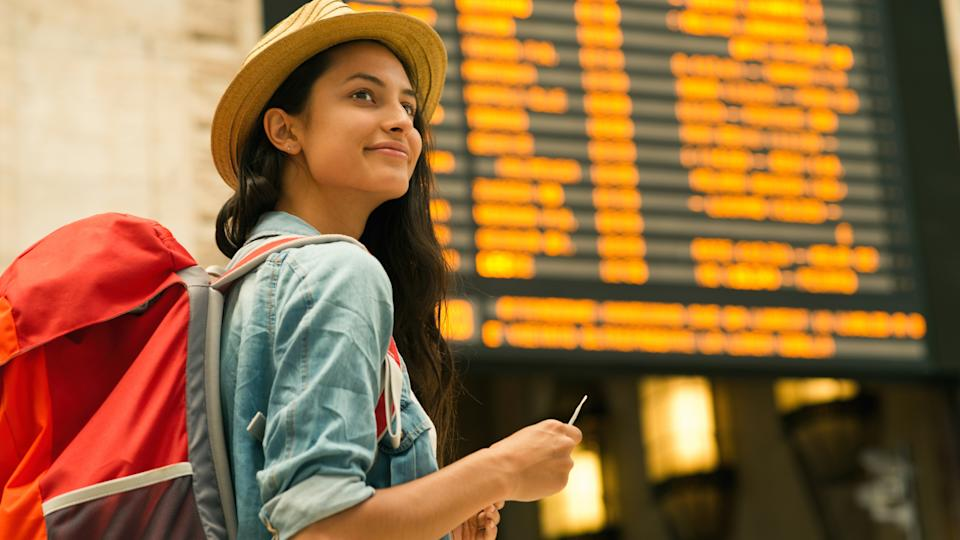 Young woman checking her train in time board.