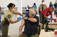 Los Angeles County Deputy Sheriff Photographer Ken Whitney, with the Scientific Services Bureau, is inoculated by Deputy Brod, left, COVID-19 mobile vaccination clinic for Sheriff's employees at the Pomona Fairplex in Pomona, Calif., Friday, March 5, 2021. More than 27 million Americans fully vaccinated against the coronavirus will have to keep waiting for guidance from U.S. health officials for what they should and shouldn't do. The Biden administration said Friday it's focused on getting the guidance right and accommodating emerging science. (AP Photo/Damian Dovarganes)