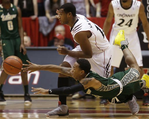 South Florida guard Anthony Collins, front, passes the ball as he falls down against Cincinnati forward Jermaine Sanders in the first half of an NCAA college basketball game, Saturday, March 9, 2013, in Cincinnati. (AP Photo/Al Behrman)