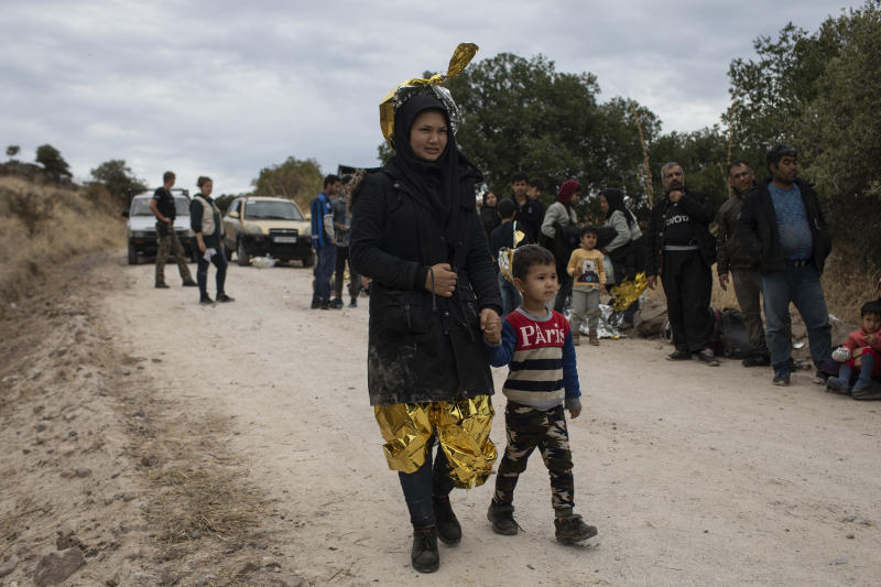 An Afghan woman with her child after arriving with other migrants and refugees after crossing a part of the Aegean Sea, from Turkey to Greece on an overcrowded dinghy, near the town of Madamados on the Greek island of Lesbos, on Monday, Oct. 7, 2019. Authorities in Greece have expanded a program to transfer migrants and refugees from overcrowded camps on the islands to the mainland amid concern that the number of arrivals from nearby Turkey could continue to rise. (AP Photo/Petros Giannakouris)