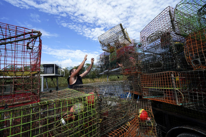 Brian Dufrene loads his crab traps on a trailer after pulling them from Bayou Dularge in anticipation of Hurricane Delta, expected to arrive along the Gulf Coast later this week, in Theriot, La., Wednesday, Oct. 7, 2020. Dufrene says he's pulled around 1,000 traps over the last three days. (AP Photo/Gerald Herbert)