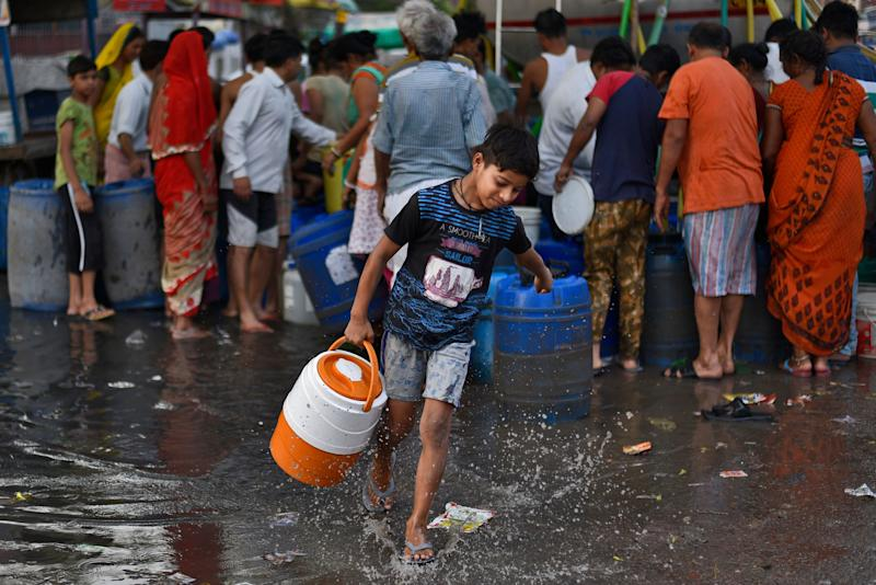 A boy carries a water container after filling it from a Delhi Jal Board tanker at Sanjay Colony in Okhla Phase II, on June 12, 2019 in New Delhi, India.