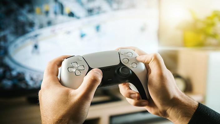Two hands holding a PlayStation controller