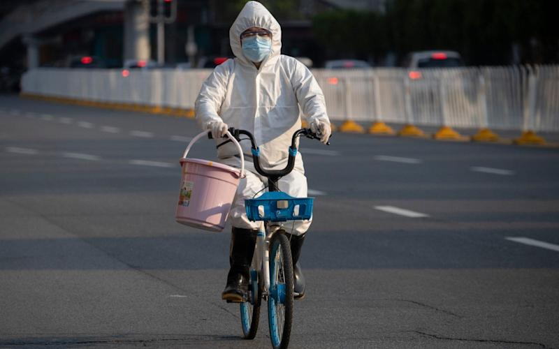 A resident in mask and suit in April in Wuhan in China, where the coronavirus originated. - Ng Han Guan /AP