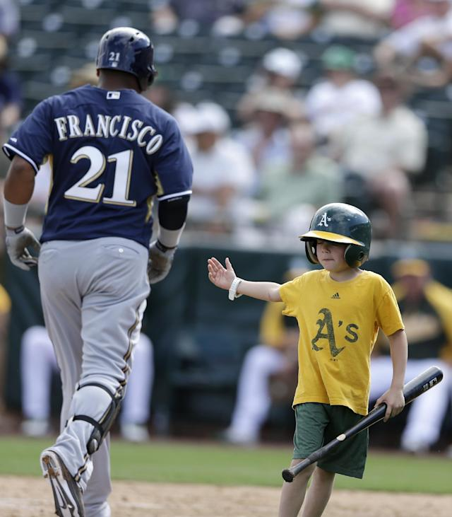 Oakland Athletics batboy Gavin Pulson, right, looks for a hand-tap from Milwaukee Brewers' Juan Francisco, left, as Francisco heads home after hitting his second home run of the day during the fourth inning of a spring training baseball game on Thursday, Feb. 27, 2014, in Scottsdale, Ariz. (AP Photo/Gregory Bull)