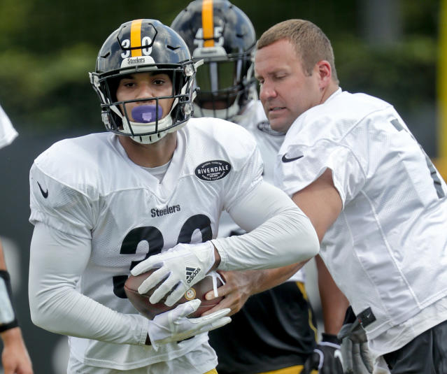 Pittsburgh Steelers running back James Conner, left, takes a handoff from quarterback Ben Roethlisberger during an NFL football practice, Wednesday, Sept. 5, 2018, in Pittsburgh. The Steelers franchise tagged star running back Le'Veon Bell still hasn't shown up for any practices, so it looks like Roethilsberger will continue to be handing off to Conner when the Steelers start the regular season against the Cleveland Browns on Sunday. (AP Photo/Keith Srakocic)
