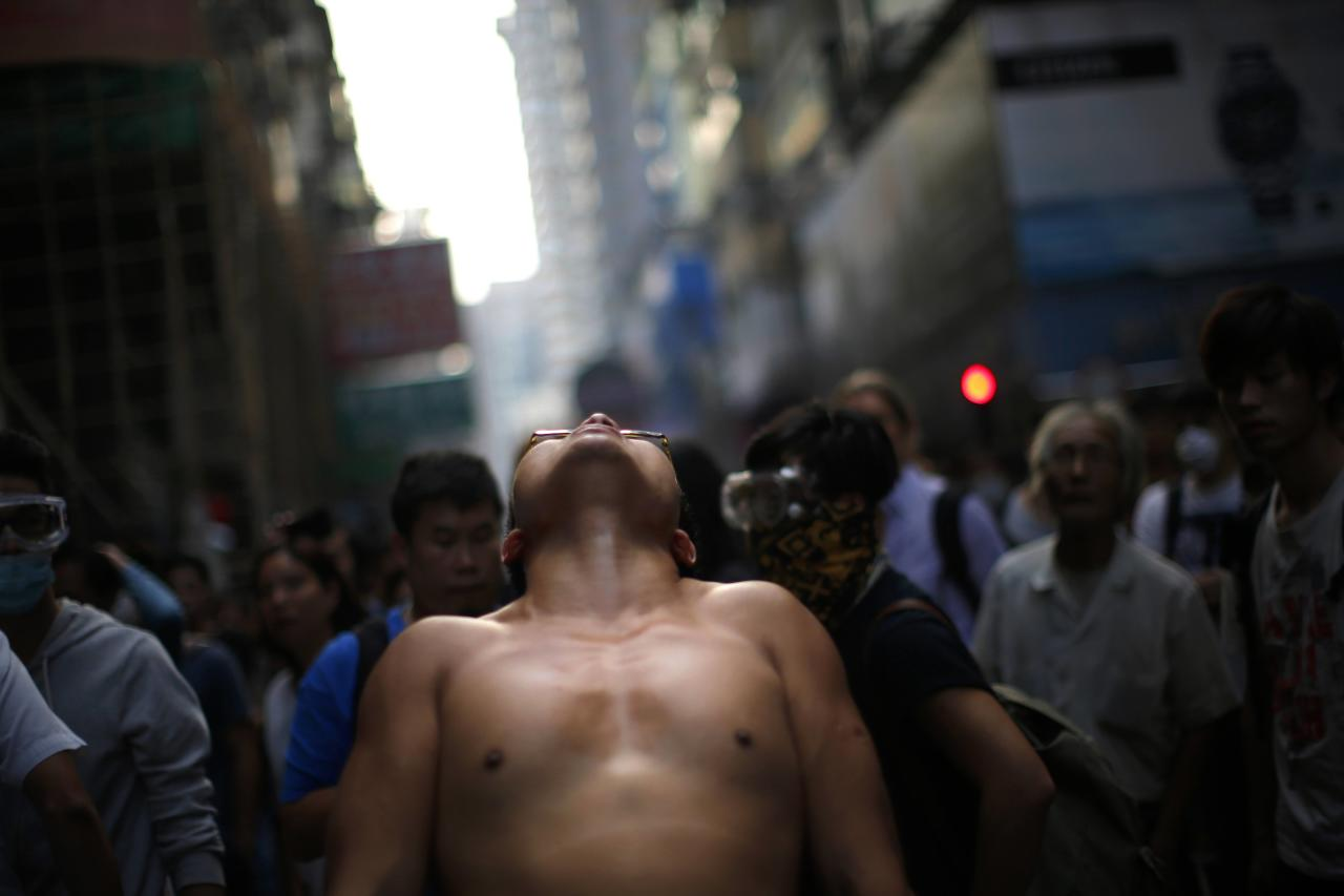 A protester reacts as police disperse the crowd after removing barricades at a protest site in Mongkok shopping district in Hong Kong October 17, 2014. Hundreds of Hong Kong police staged a dawn raid on Friday on one of the key sites occupied by pro-democracy protesters, removing barricades from roads and clearing out most of the demonstrators in an another setback for their movement. The operation in the gritty working class area of Mong Kok, across the harbour from the main demonstration zone near the office of Hong Kong's leader, came while many protesters were asleep in their tents. REUTERS/Carlos Barria (CHINA - Tags: CIVIL UNREST POLITICS)
