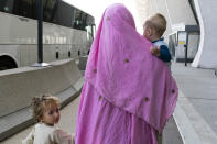 Families evacuated from Kabul, Afghanistan, walk through the terminal before boarding a bus after they arrived at Washington Dulles International Airport, in Chantilly, Va., on Friday, Aug. 27, 2021. (AP Photo/Jose Luis Magana)
