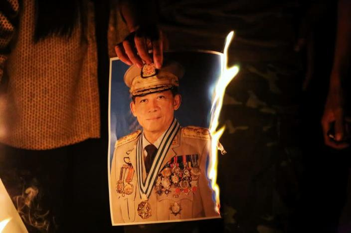 People burn a portrait of Army chief General Min Aung Hlaing as they protest against the military coup, in Mandalay