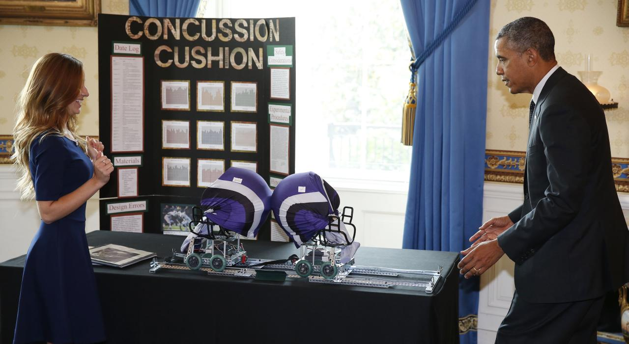 U.S. President Barack Obama listens to Maria Haynes, of Santa Cruz, California, talk about her concussion cushion football helmet as he hosts the 2014 White House Science Fair in the Blue Room at the White House in Washington May 27, 2014. REUTERS/Larry Downing (UNITED STATES - Tags: POLITICS SPORT FOOTBALL SCIENCE TECHNOLOGY)