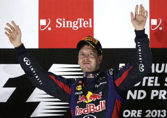 Red Bull Formula One driver Sebastian Vettel of Germany waves on the podium after winning the Singapore F1 Grand Prix at the Marina Bay street circuit in Singapore September 22, 2013. REUTERS/Pablo Sanchez (SINGAPORE - Tags: SPORT MOTORSPORT F1)