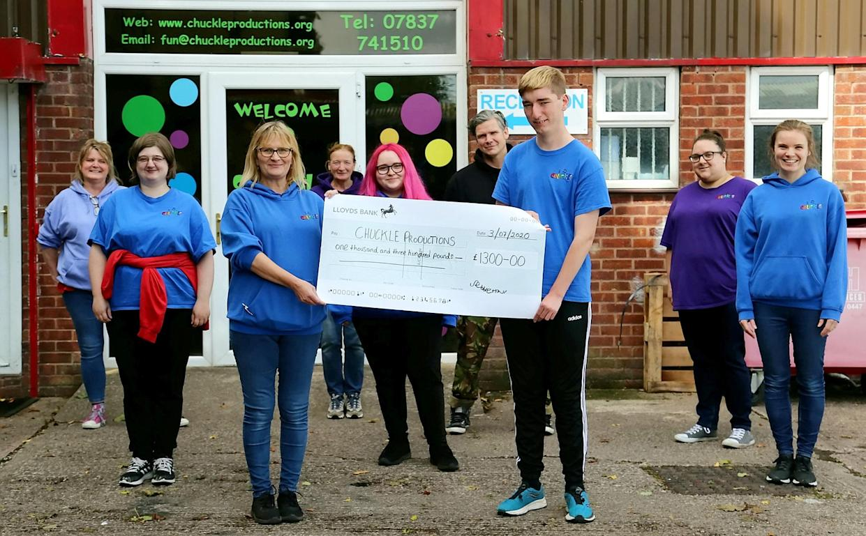 Sebbie Hall presents a cheque to Chuckle Productions. (Supplied Ashley Hall/SWNS)
