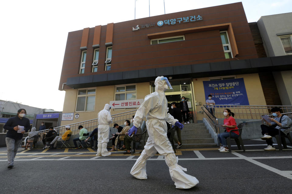 A health official wearing protective gear passes by people sitting and waiting for test for the new coronavirus at a public health center in Goyang, South Korea, Thursday, May 28, 2020. South Korea on Thursday reported its biggest jump in coronavirus cases in more than 50 days, a setback that could erase some of the hard-won gains that have made it a model for the rest of the world. (AP Photo/Ahn Young-joon)