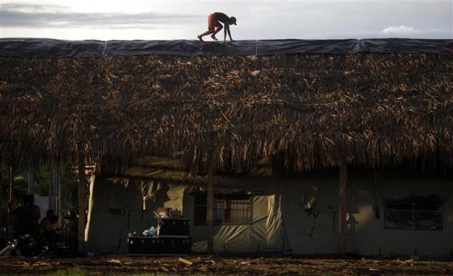 "A man works on the roof of a campaign hospital built by the ""Expedicionarios da Saude"" (Brazilian Health Expeditions) on the first day of the medical expedition at the Kayapo tribe in Sao Felix, northern Brazil, April 21, 2011."