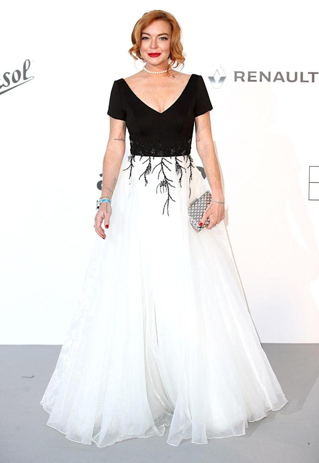 <p>Who's that lady? Lindsay Lohan kept it classy for the 2017 Cannes amfAR Gala in a demure black-and-white gown. The <em>Mean Girls</em> star completed her look with a simple pearl choker, silver clutch, and bold red lips. (Photo: Mike Marsland/WireImage) </p>