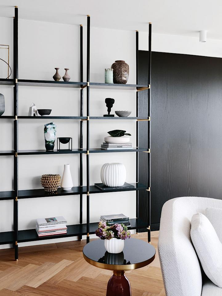 "<p>A floor-to-ceiling wall unit will clear excess clutter from your useable surfaces and tables throughout the living room. This is obviously good for functional reasons (like having a place to put down your cocktail), but it also dresses up the walls. Designed by <a href=""https://arentpyke.com/"" target=""_blank"">Arent & Pyke</a>, this shelving unit is sophisticated and spacious on it's own, while also providing another place to display decorative objects.</p><p><a class=""body-btn-link"" href=""https://go.redirectingat.com?id=74968X1596630&url=https%3A%2F%2Fwww.cb2.com%2Fstairway-black-cabinet-96%2Fs199103&sref=http%3A%2F%2Fwww.housebeautiful.com%2Froom-decorating%2Fliving-family-rooms%2Fg28498879%2Fliving-room-storage-ideas%2F"" target=""_blank"">BUY NOW</a> <strong><em>CB2 Cabinet Shelving Unit, $699</em></strong></p>"