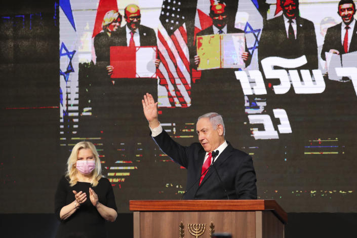 Israeli Prime Minister Benjamin Netanyahu with his wife Sara Netanyahu waves to his supporters after the first exit poll results for the Israeli parliamentary elections at his Likud party's headquarters in Jerusalem, Wednesday, March. 24, 2021. (AP Photo/Ariel Schalit)