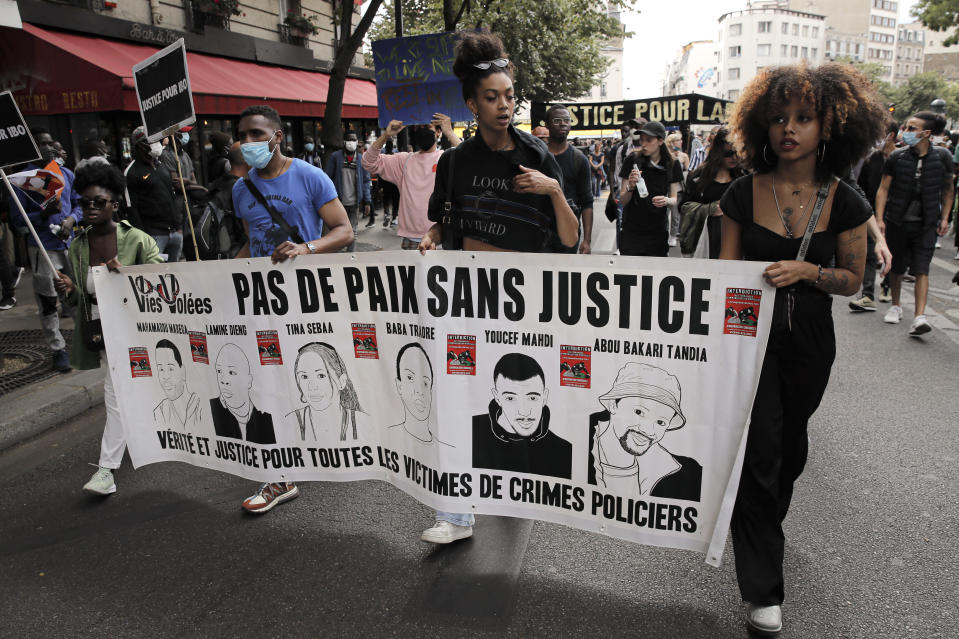 """People march holding a banner that reads """"No country without justice- Truth and justice for all the victims of police crimes"""" during a protest in memory of Lamine Dieng, a 25-year-old Franco-Senegalese who died in a police van after being arrested in 2007, in Paris, Saturday, June 20, 2020. Multiple protests are taking place in France on Saturday against police brutality and racial injustice, amid weeks of global anger unleashed by George Floyd's death in the US. (AP Photo/Christophe Ena)"""