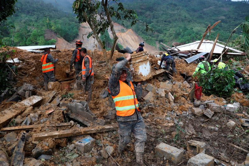 Soldiers remove debris and mud from an area hit by a mudslide, caused by heavy rains brought by Storm Eta, as the search for victims continue in the buried village of Queja