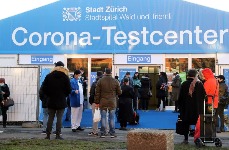 A medical worker talks to people queueing in front of a COVID-19 testing site of the Stadtspital Waid and Triemli hospital in Zurich
