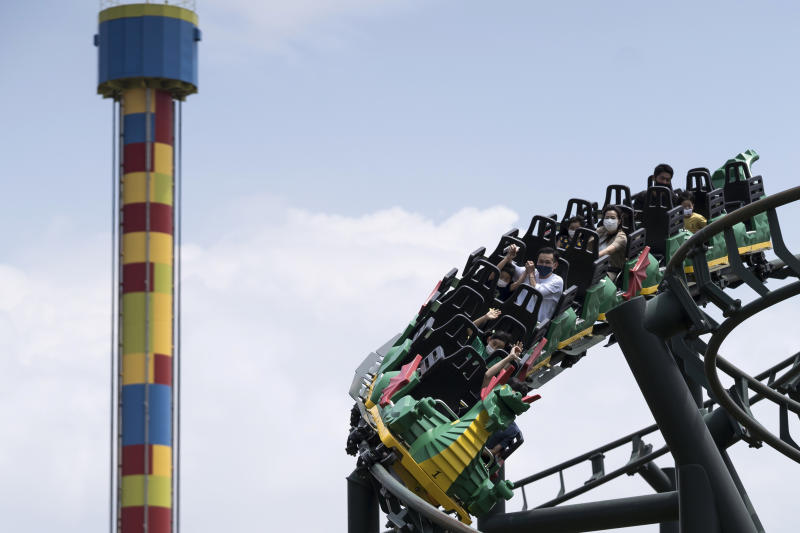 Visitors wearing face masks ride the Dragon's Apprentice roller coaster inside the Legoland Japan theme park on May 23, 2020 in Nagoya, Japan (Getty)