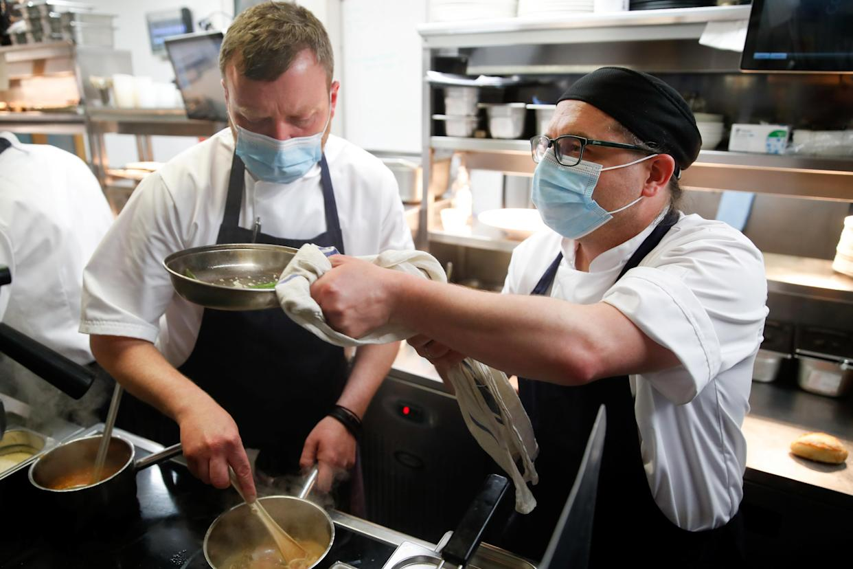 Staff members wear masks while they work at Loxleys Restaurant & Wine Bar, as coronavirus disease (COVID-19) restrictions continue to ease, in Stratford Upon Avon, Britain, May 17, 2021. REUTERS/Andrew Boyers