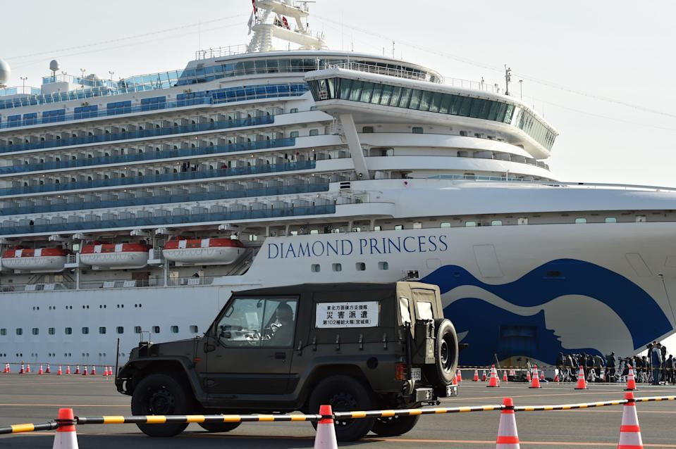 A Japanese Self-Defense Forces Health Corps vehicle enters a cordoned-off area at the Daikoku Pier Cruise Terminal where the quarantined Diamond Princess cruise ship (rear) is anchored, in Yokohama on February 7, 2020, as over 3,700 people remain quarantined onboard due to fears of the new coronavirus. - At least 61 people on board a cruise ship off Japan have tested positive for the new coronavirus, the government said February 7, as thousands of passengers and crew face a two-week quarantine. (Photo by Kazuhiro NOGI / AFP) (Photo by KAZUHIRO NOGI/AFP via Getty Images)