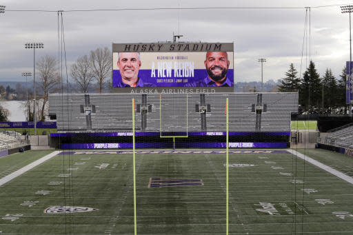 Photos of Washington head coach Chris Petersen, left, and defensive coordinator Jimmy Lake are shown on the scoreboard at Husky Stadium after the announcement that Petersen is leaving his position and that Lake is assuming it, Tuesday, Dec. 3, 2019, in Seattle. Petersen unexpectedly resigned at Washington on Monday, a shocking announcement with the Huskies coming off a 7-5 regular season and bound for a sixth straight bowl game under his leadership. Petersen will coach Washington in a bowl game, his final game in charge. (AP Photo/Elaine Thompson)