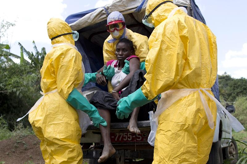 Health workers assist a patient suspected of having Ebola on their way to a treatment centre run by the French Red Cross in Patrice, Guinea, on November 21, 2014 (AFP Photo/Kenzo Tribouillard)