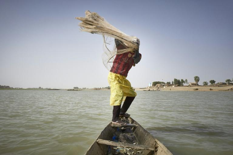 A fisherman on his pirogue throws a net in the Niger river in Mopti