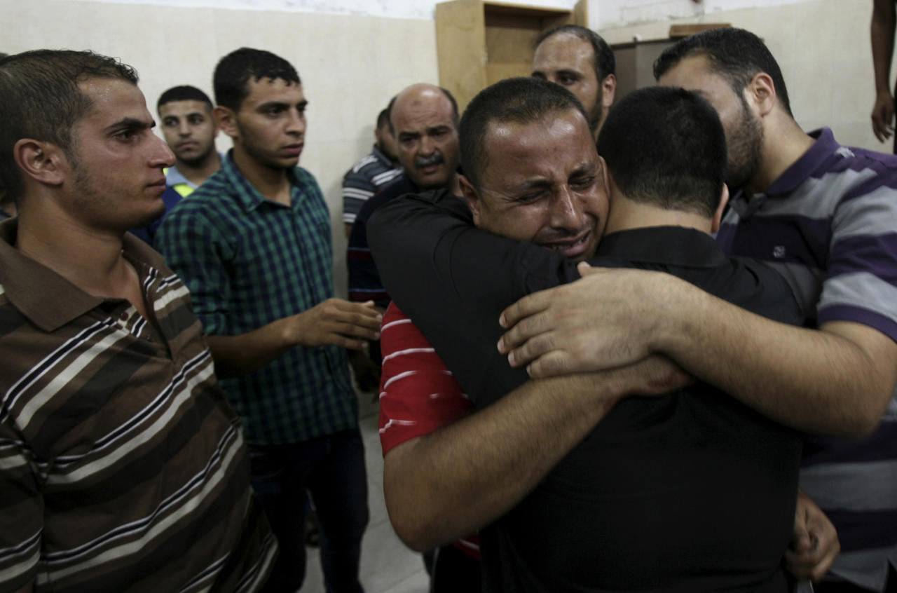 Palestinian relatives comfort each other after they saw the body of Ahmad Jarboua, 25, who was killed in an Israeli strike with other two people, at Najar hospital in Rafah refugee camp, in the southern Gaza Strip, Tuesday, Aug. 26, 2014. Three men were killed and five were wounded in a strike on a group of men east of Rafah near the waste water treatment plant, according to Gaza health official Ashraf al-Kidra. (AP Photo/Eyad Baba)