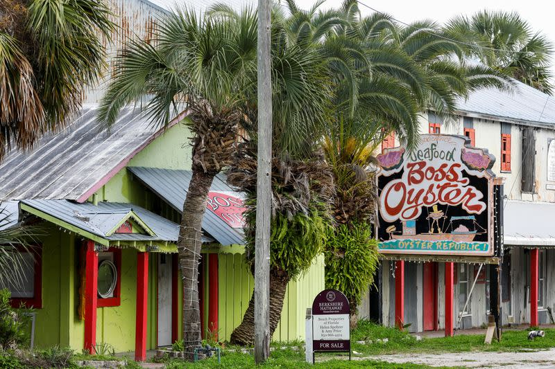 """A """"for sale"""" sign is seen outside the Boss Oyster restaurant, which has been closed since Hurricane Michael hit the area in October 2018, in Apalachicola, Florida"""