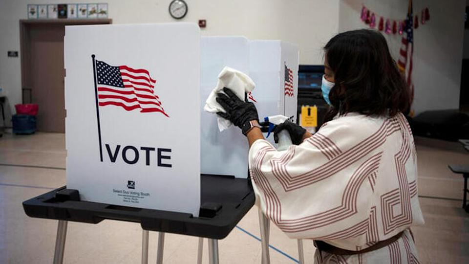 Election worker Gisela Alberg cleans a voting booth at Sonoma Elementary School during the primary election in Las Cruces, New Mexico, U.S., June 2, 2020. (Paul Ratje/Reuters)