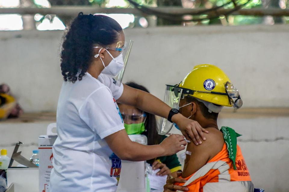 Workers of cement plant receives their COVID-19 vaccine in Antipolo City, Philippines.