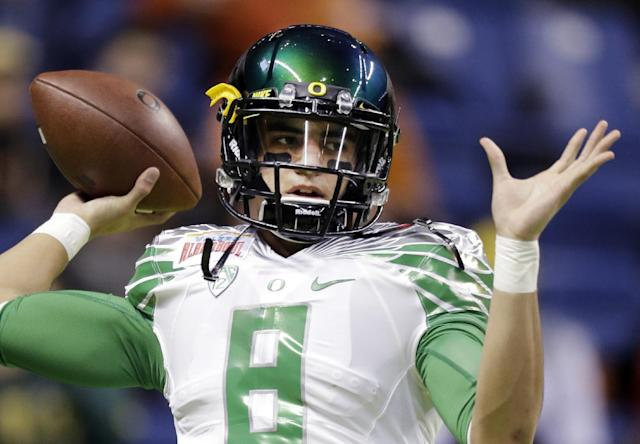 FILE-This Dec. 30, 2013 file photo shows Oregon's Marcus Mariota warms up for the Valero Alamo Bowl NCAA college football game against Texas in San Antonio. All eyes will be on Mariota when the Ducks take the field this season. The junior quarterback could have bolted for the NFL this spring but he decided to stay with the Ducks, who were ranked as high as No. 2 last season before two losses took them out of contention for the national championship. (AP Photo/Eric Gay,File)