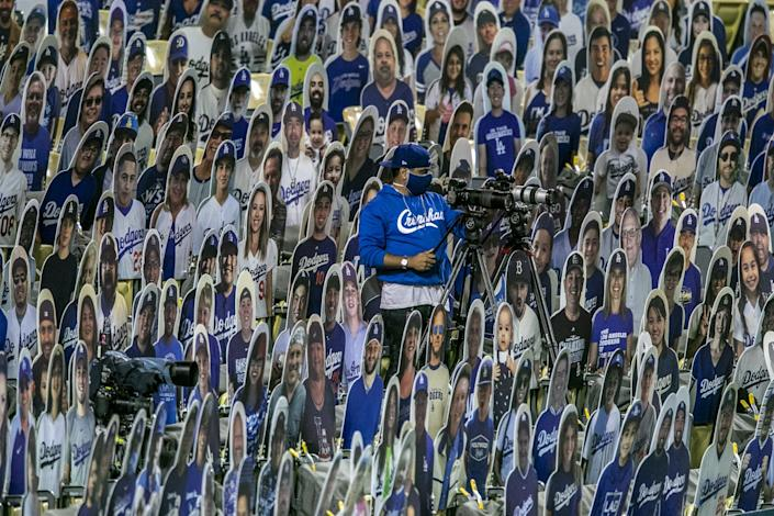 A man and his camera are perched in stadium seating amid numerous cardboard likenesses of fans.