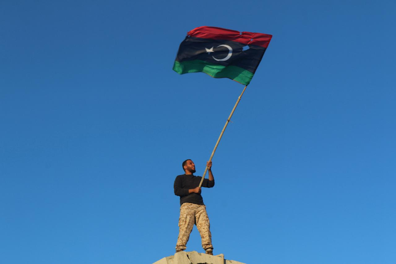 A fighter of Libyan forces holds a Libyan flag as he celebrates after forces finished clearing Ghiza Bahriya, the final district of the former Islamic State stronghold of Sirte, Libya December 6, 2016. REUTERS/Hani Amara        TPX IMAGES OF THE DAY