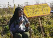 Climate activists Vanessa Nakate from Uganda reads an extract from her book at an activists camp near the Garzweiler open-cast coal mine in Luetzerath, western Germany, Saturday, Oct. 9, 2021. The village of Luetzerath, now almost entirely abandoned as the mine draws ever closer, will be the latest village to disappear as coal mining at the Garzweiler mine expands. Garzweiler, operated by utility giant RWE, has become a focus of protests by people who want Germany to stop extracting and burning coal as soon as possible. (AP Photo/Martin Meissner)