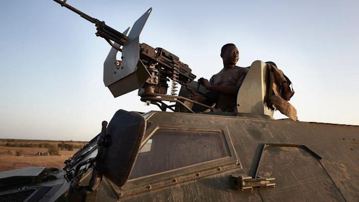 A soldier of the Burkina Faso Army poses on the top of an armoured vehicle during a patrol in the Soum region in northern Burkina Faso on November 12, 2019.