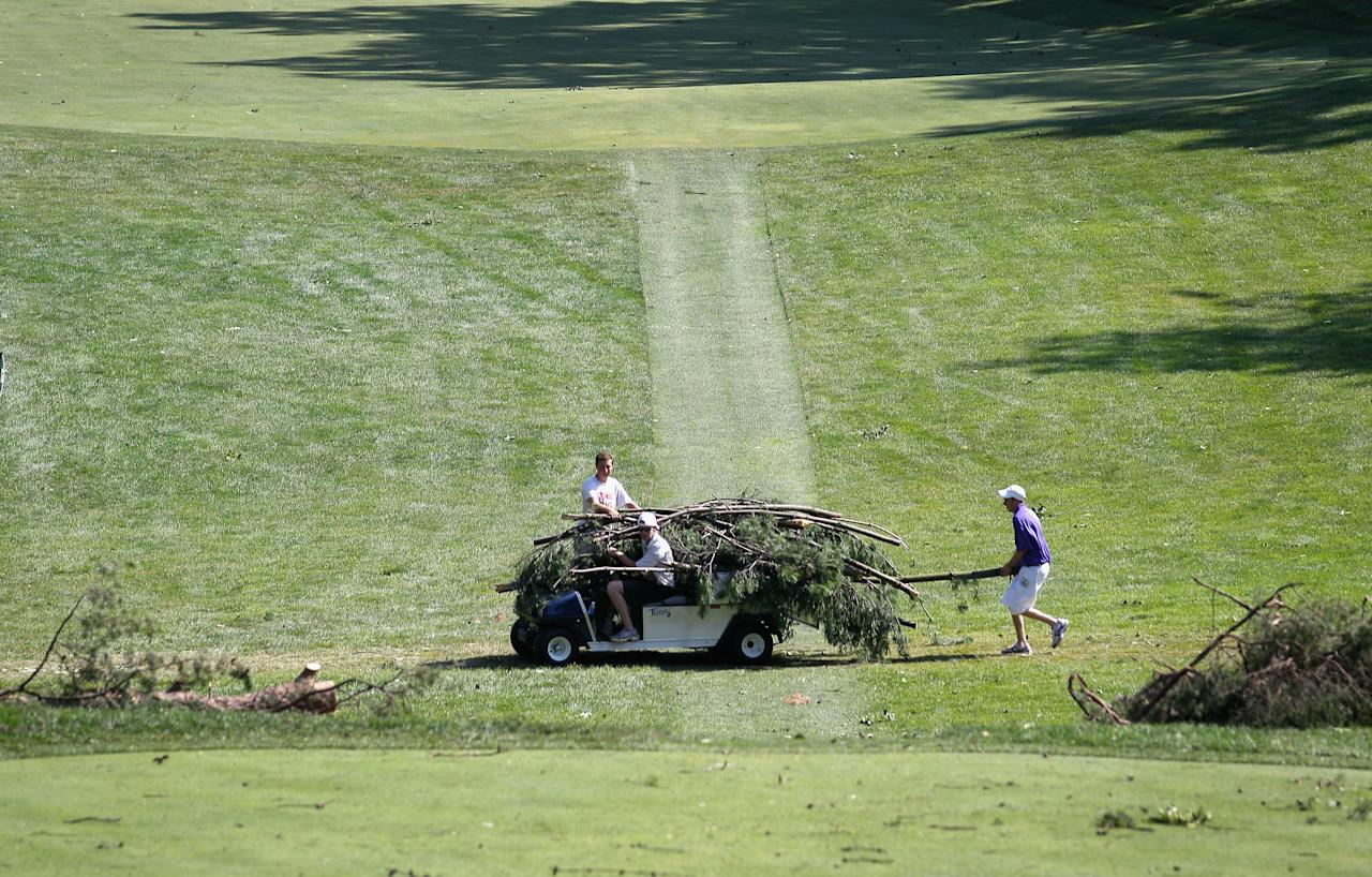 BETHESDA, MD - JUNE 30:  Workers remove debris from the 14th fairway due to overnight storm damage that delayed the start of Round Three of the AT&T National at Congressional Country Club on June 30, 2012 in Bethesda, Maryland. Overnight storms knocked out power to up to a million people in the D.C. area and course officials have  closed the course to spectators. (Photo by Rob Carr/Getty Images)