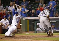 Chicago Cubs' John Baker, left, scores the game winning run off a sacrifice fly by Starlin Castro, as the ball gets past Colorado Rockies catcher Wilin Rosario (20) during the 16th inning of a baseball game Wednesday, July 30, 2014, in Chicago. The Cubs' won 4-3. (AP Photo/Charles Rex Arbogast)