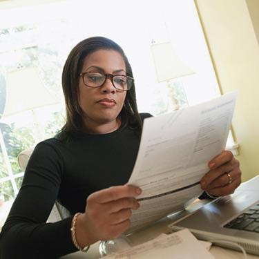 Woman-looking-at-paperwork-in-home-office_web